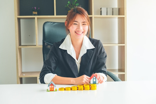 Frauen-immobilienmakler halten ein kleines hausmodell in ihrer hand- und goldmünzenstapel