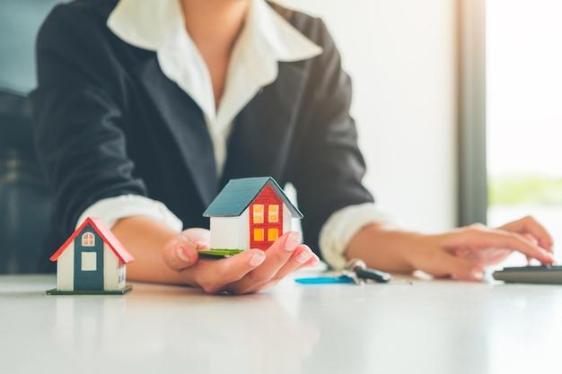 Frauen-immobilienmakler halten ein kleines hausmodell in ihrer hand