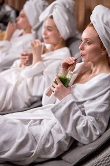 Frauen in bademänteln verbringen zeit im spa-resort-hotelsalon und genießen nach schönheitsbehandlungen natürlichen bio-saft. körperpflege, wellness und entspannungskonzept. fokus auf rothaarige frau mit handtuch auf dem kopf