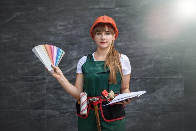 Frauen in baukleidung und helm mit farbmuster zur reparatur bereit