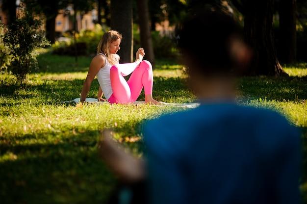 Frauen in den sportsuits, die unterschiedliches yoga üben, werfen im park auf