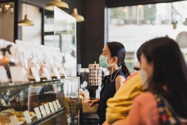 Frauen in der medizinischen maske, die getränk am kaffeeschalter bestellt.