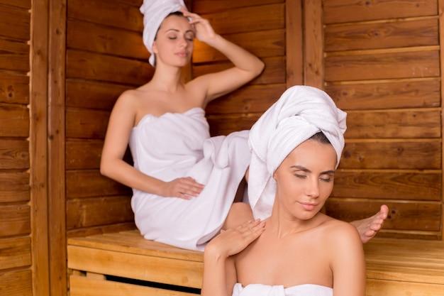 Frauen in der sauna. zwei attraktive frauen, die in ein handtuch gewickelt sind, entspannen sich in der sauna und halten die augen geschlossen