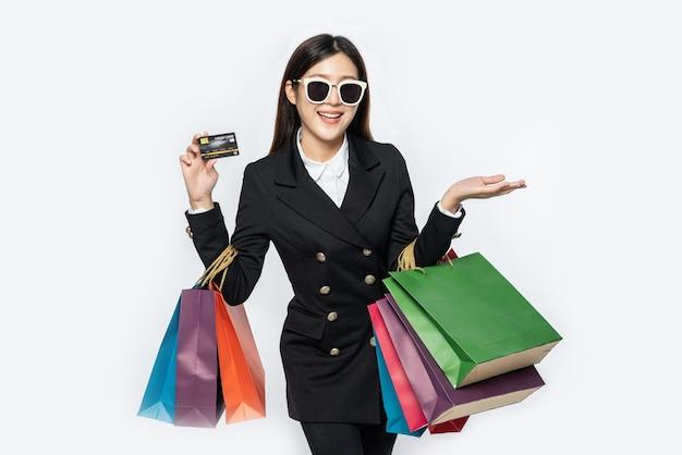 Frauen in dunklen brillen tragen einkäufe, tragen kreditkarten und viele taschen