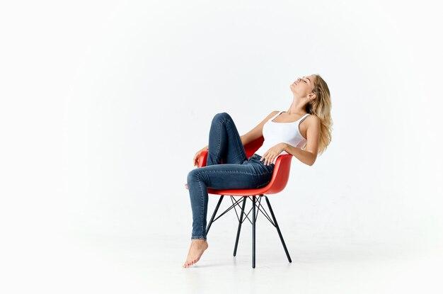 Frauen in einem roten sessel in einem hellen raumporträt-innenmodell. hochwertiges foto