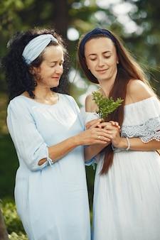 Frauen in einem sommerwald. dame in einem blauen kleid. familie posiert und umarmt.