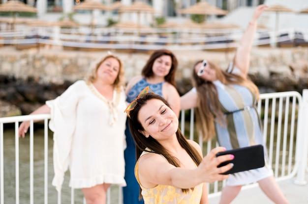 Frauen in freizeitkleidung, die fotos machen und reisen
