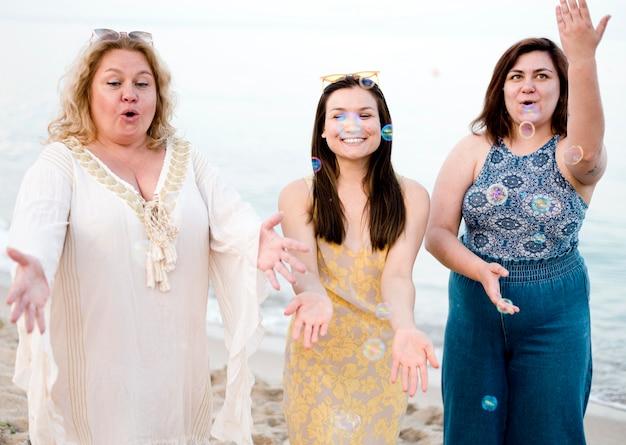 Frauen in freizeitkleidung spielen mit blasen