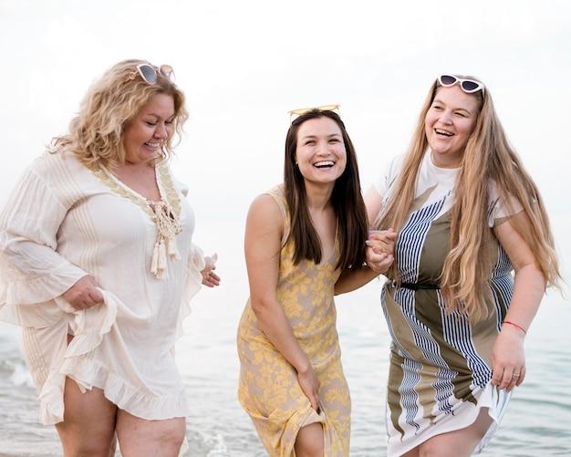 Frauen in freizeitkleidung stehen mit den füßen im wasser