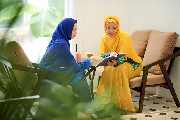 Frauen in hijabs diskutieren interessantes buch
