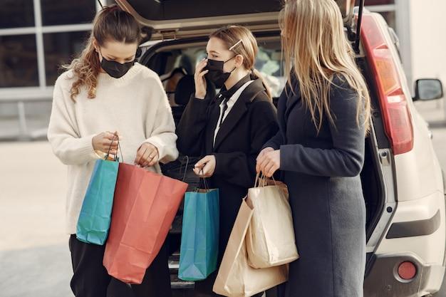 Frauen in masken gehen mit einkaufstüten nach draußen