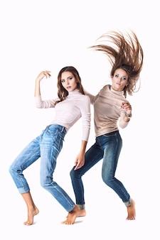 Frauen in modischer kleidung in jeans im studio an einer weißen wand in verschiedenen posen