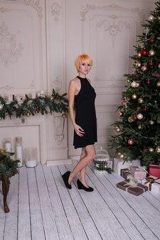Frauen in schwarzen kleidern in der nähe von geschmücktem weihnachtsbaum