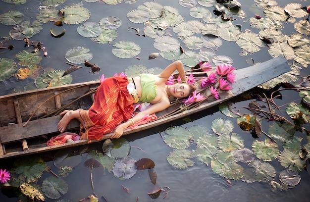 Frauen in traditionellem kostüm thailands, das auf boot durch lotos von der draufsicht liegt