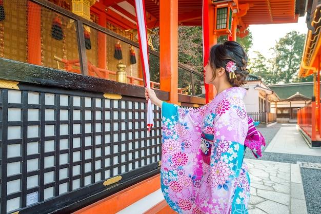 Frauen in traditionellen japanischen kimonos am fushimi inari-schrein in kyoto, japan