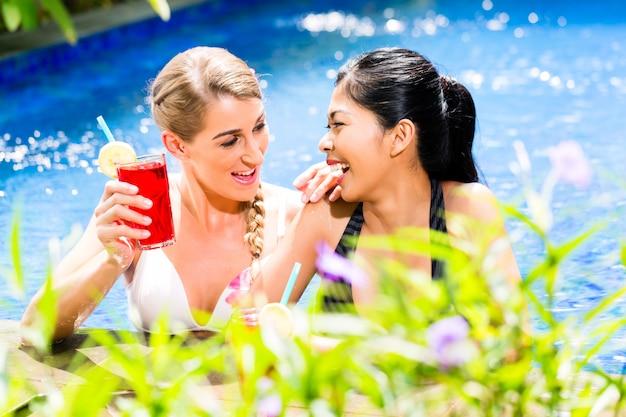 Frauen in trinkenden cocktails des asiatischen hotelpools