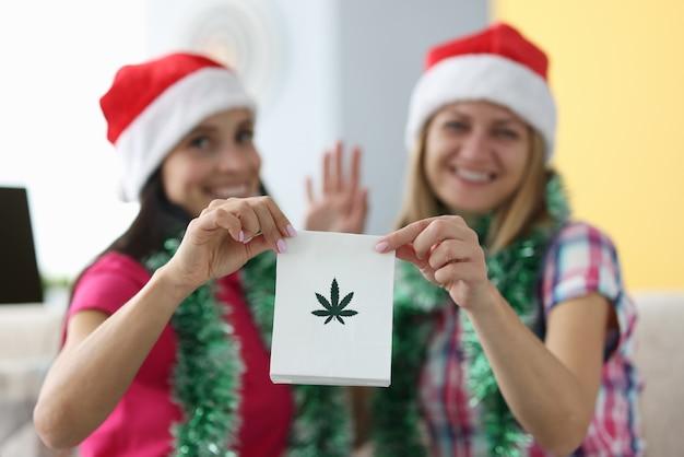 Frauen in weihnachtshüten halten eine tüte marihuana-blätter und winken