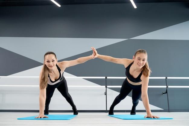 Frauen klatschen in die hände und halten sich in der plankenposition