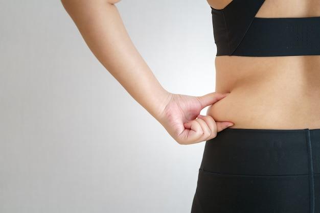 Frauen körperfett bauch. übergewichtige frauenhand, die übermäßiges bauchfett hält. diät-lebensstil-konzept