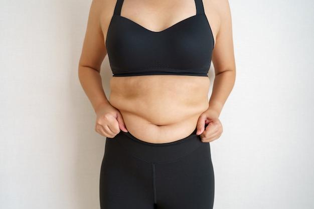 Frauen körperfett bauch. übergewichtige frauenhand, die übermäßiges bauchfett hält.