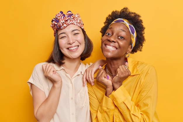 Frauen lächeln im großen und ganzen, haben spaß zusammen und sind froh, gute optimistische nachrichten zu hören, die für das fotografieren posieren. diverse studentinnen freuen sich über erfolgreiche prüfungen. ethnizität und emotionen konzept