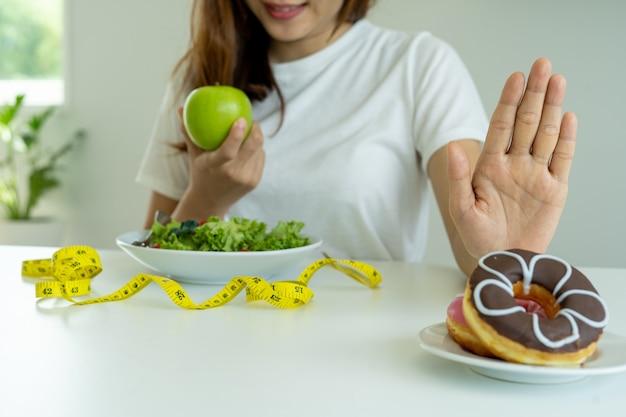 Frauen lehnen junk food oder ungesunde lebensmittel wie donuts ab und wählen gesunde lebensmittel wie grüne äpfel und salate.