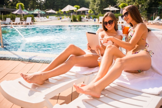 Frauen liegen auf chaiselongue und benutzen digitale tablets.