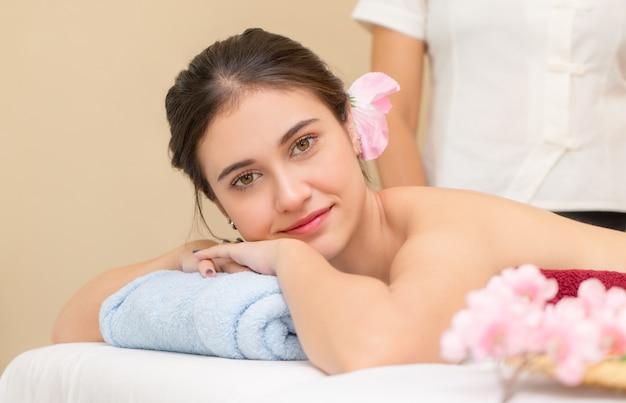 Frauen liegen auf dem bett, das bereit ist, kurkurs mit dem massage-therapeuten auf dem hintergrund zu nehmen