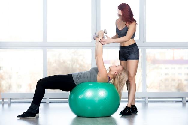 Frauen machen pilates übungen im fitnessstudio