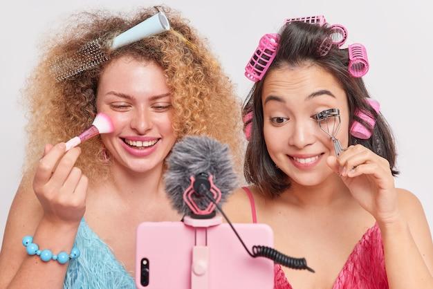 Frauen make-up auftragen gesichtspuder verwenden wimpernzange video-blog aufzeichnen auf social media teilen vor dem smartphone stehen frisur isoliert auf weiß machen