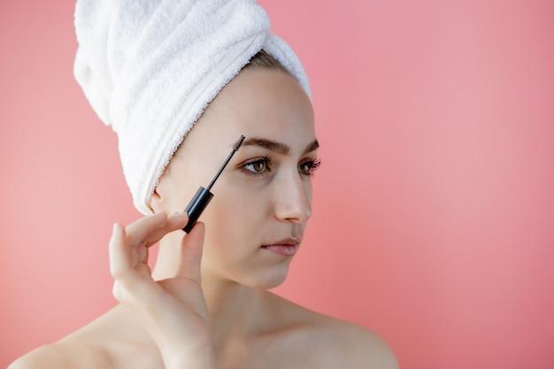 Frauen make-up. nahaufnahme des jungen weiblichen modellgesichtes mit glatter weicher gesunder haut und frischem make-up. schöne mädchenhand mit augenbrauen-gel-bürste für augenbrauen. schönheitswerkzeuge. hochauflösendes bild.
