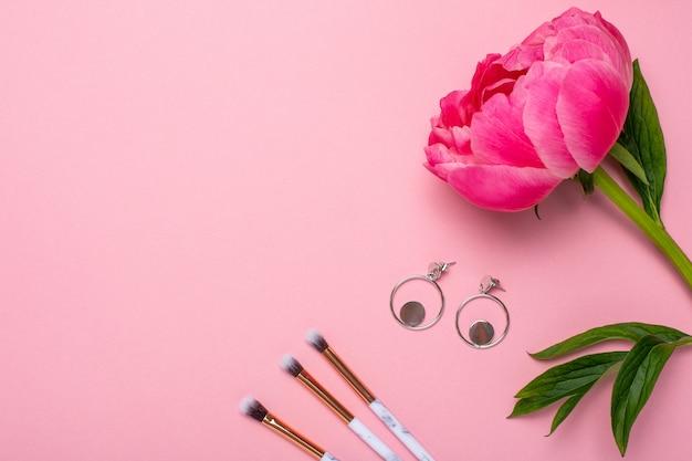 Frauen make-up pinsel und ohrringe mit einer schönen blumenpfingstrose mit kopierraum für ihren text