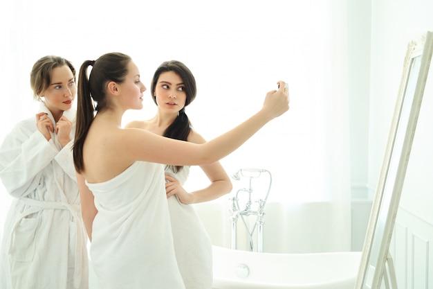 Frauen mit bademantel und handtüchern