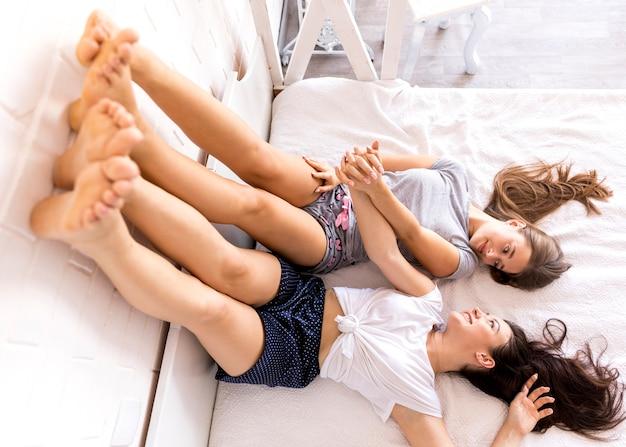Frauen mit beinen auf dem bett liegend