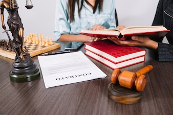 Frauen mit Büchern bei Tisch mit Smartphone, Statue, Dokument und Schach