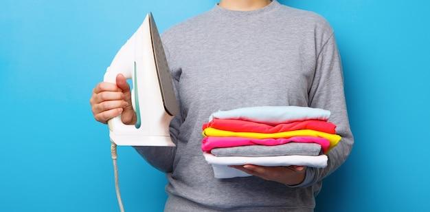 Frauen mit bügeleisen und kleiderhaufen in den händen. konzept der hausarbeit.