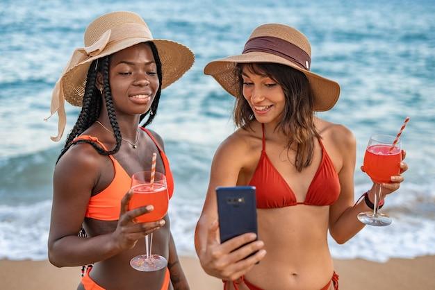 Frauen mit cocktails, die ein selfie gegen das meer machen