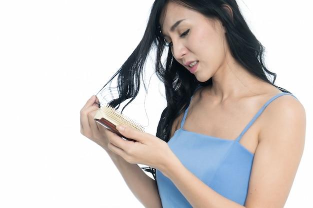 Frauen mit dem haarproblem, das in der hand verlusthaar hält, isloated auf weißem hintergrund