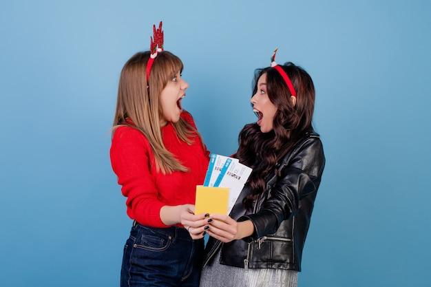Frauen mit den flugtickets und pass, die die lustigen weihnachtsbänder lokalisiert über blau tragen