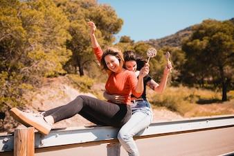 Frauen mit den Lutschern, die auf Schutzplanke sitzen