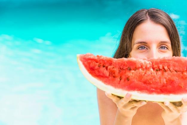 Frauen mit der wassermelone, die nahe swimmingpool steht
