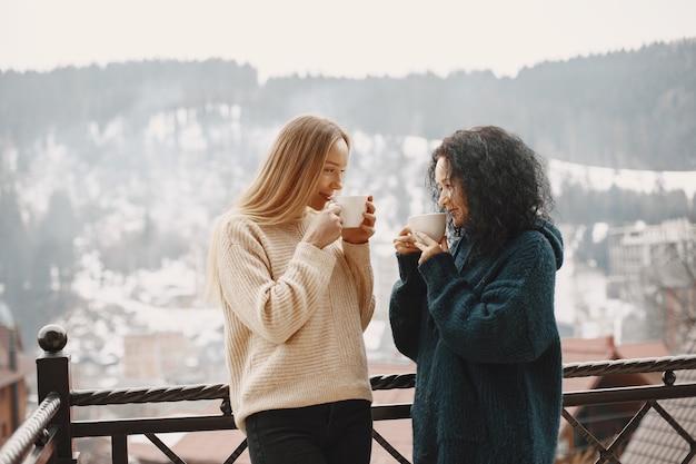 Frauen mit einer tasse kaffee. wundervoller urlaub in den bergen. verschneites wetter.