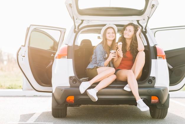 Frauen mit essen am kofferraum
