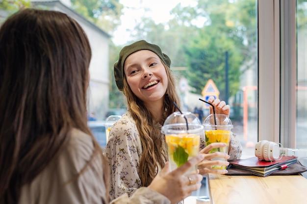 Frauen mit frischen getränken sprechen im café
