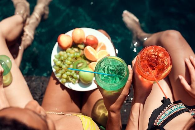 Frauen mit früchten und cocktails am pool