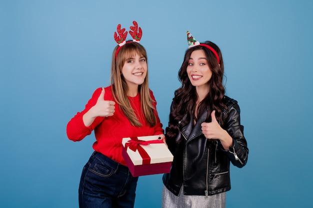 Frauen mit geschenkbox mit dem band, welches die lustigen weihnachtsbänder lokalisiert über blau trägt