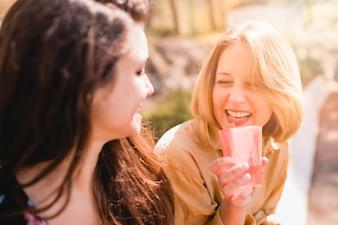 Frauen mit Getränk lachen