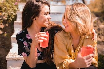 Frauen mit Getränken, die einander betrachten