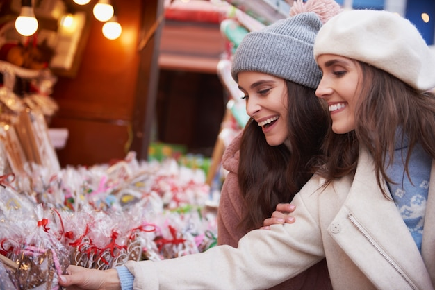 Frauen mit großer auswahl an süßigkeiten auf dem weihnachtsmarkt