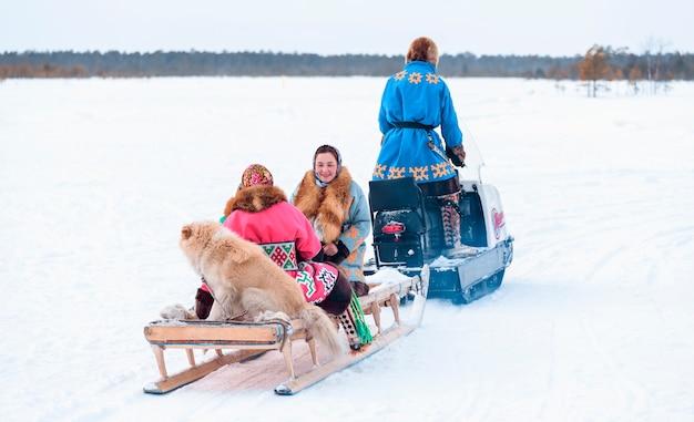 Frauen mit hund auf narts mit schneemobil. feiertag des tages der nordvölker der rentiere.